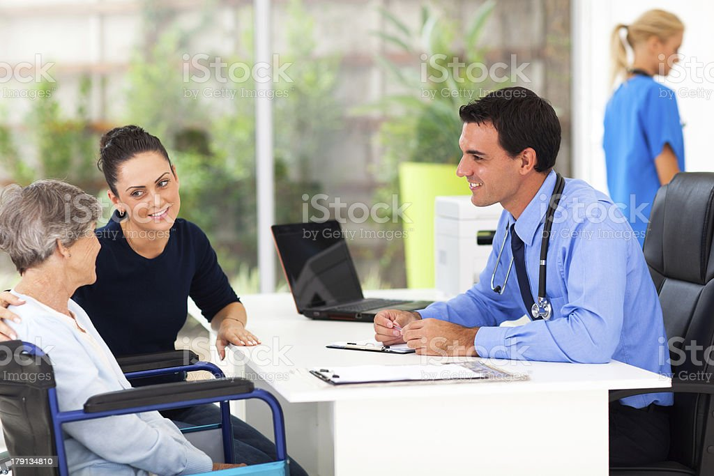 senior woman and her daughter in doctor's office royalty-free stock photo