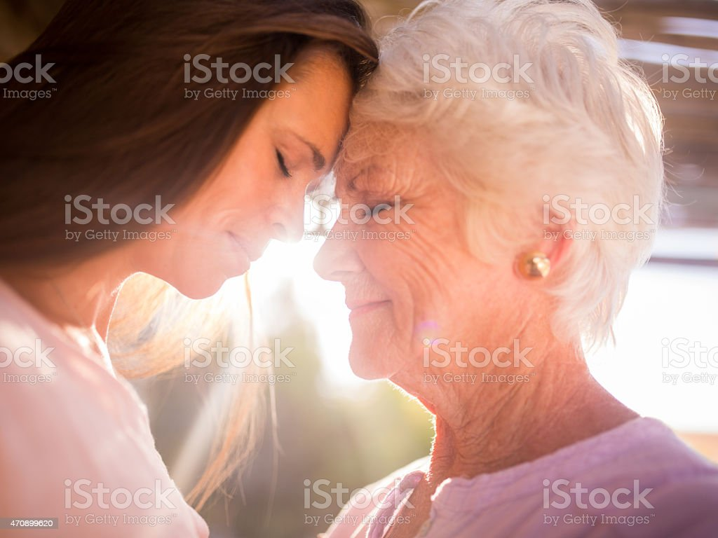 Senior woman and her loving adult daughter outdoors stock photo