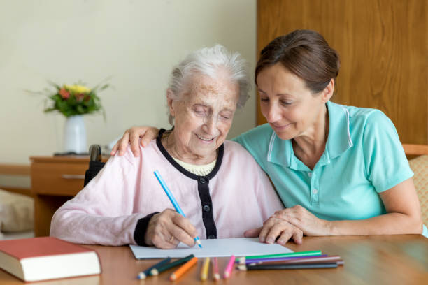 Senior Woman and Home Caregiver - Dementia and Occupational Therapy stock photo