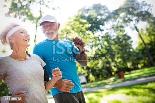 Senior woman and man running doing fitness exercises outdoor