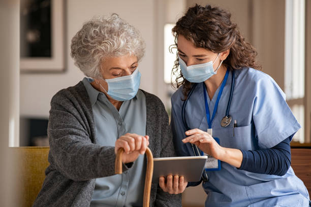 Senior woman and nurse using digital tablet at home during consult stock photo
