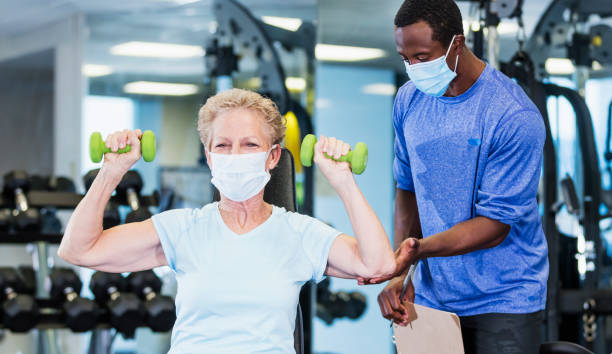 Senior woman and personal trainer in gym, wearing masks stock photo