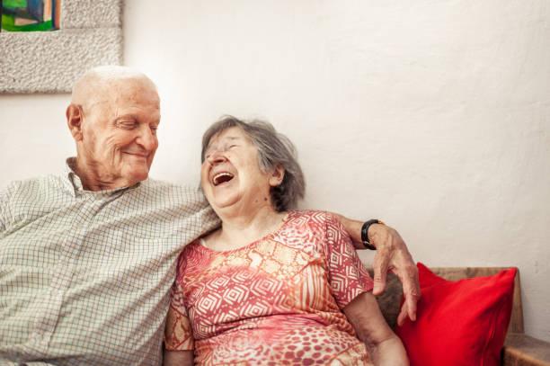 senior woman and senior man sitting on the sofa - sud europeo foto e immagini stock