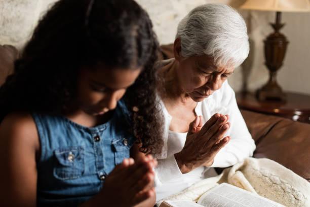 Senior woman and teen girl praying together stock photo