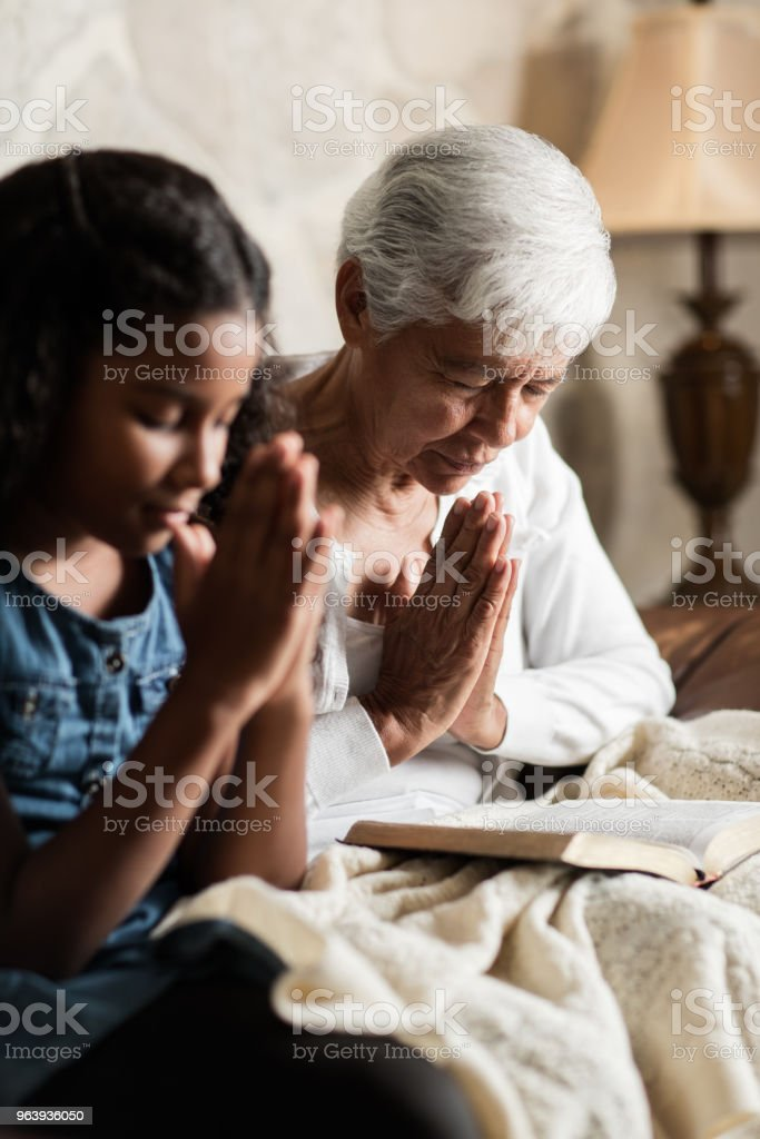 Senior woman and teen granddaughter praying with eyes closed - Royalty-free 65-69 Years Stock Photo
