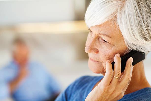 Senior Frau beantworten Smartphone mit Mann im Hintergrund – Foto