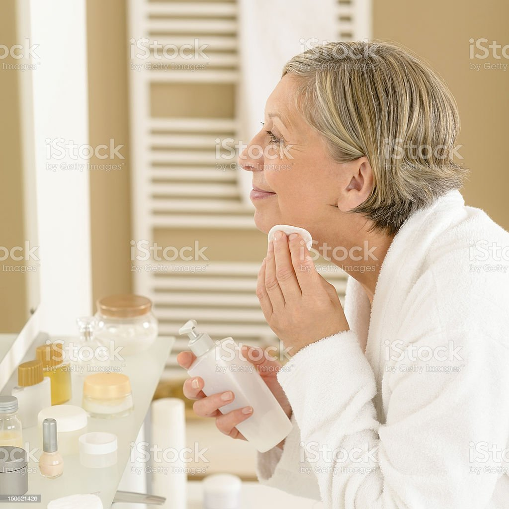 Senior woman apply face cleaning lotion royalty-free stock photo