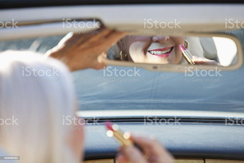 Senior woman apply lipstick in convertible royalty-free stock photo