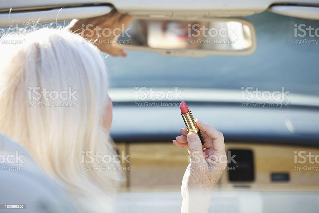 Sênior mulher aplicar batom em Conversível - foto de acervo