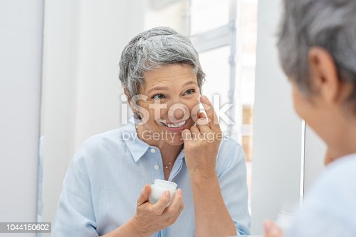 istock Senior woman applying anti aging cream 1044150602