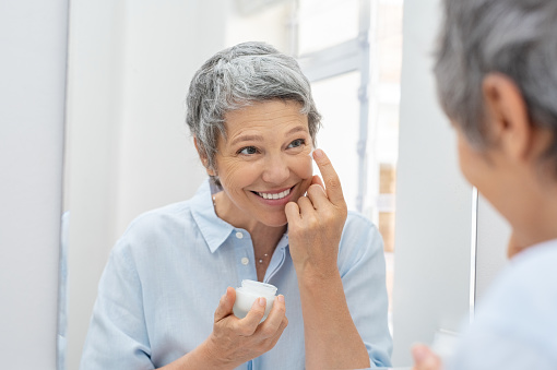 Happy mature woman applying face lotion while looking herself in the bathroom mirror. Senior woman applying anti aging moisturizer on her face. Smiling lady holding little jar of skin cream and applying lotion during the morning routine.