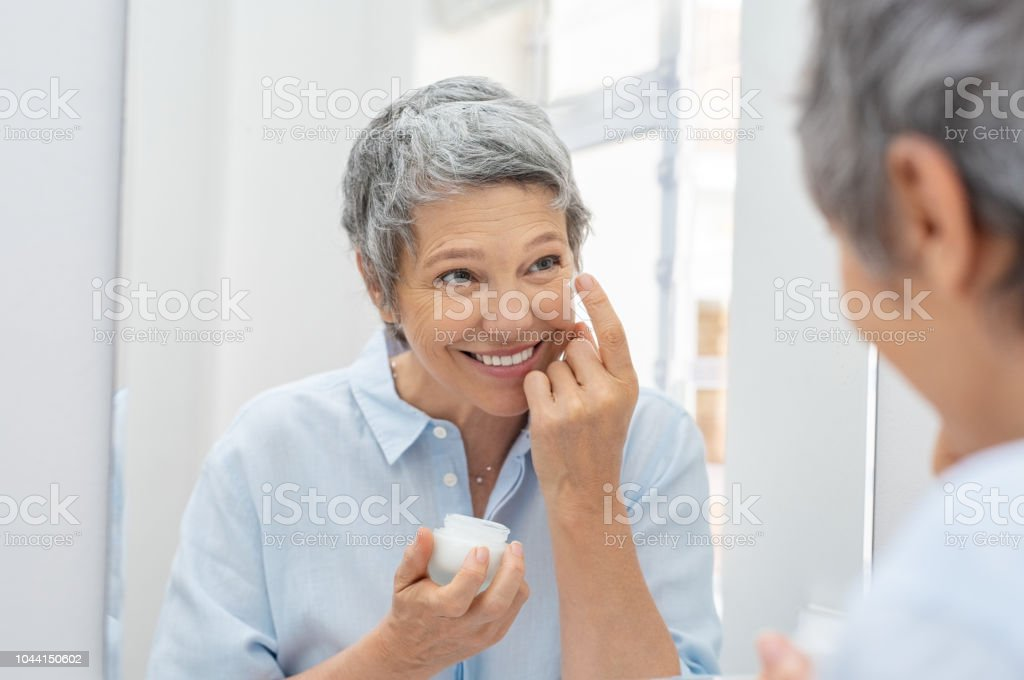 Senior woman applying anti aging cream stock photo