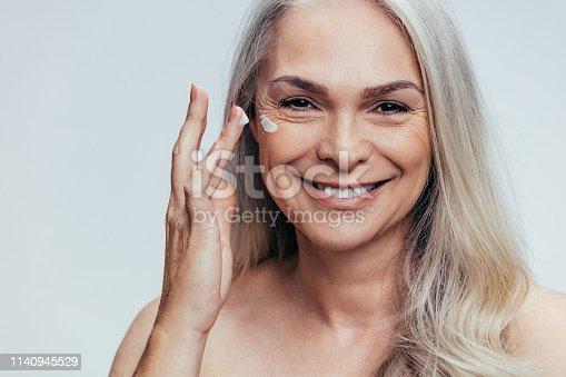 istock Senior woman applying anti aging cream 1140945529