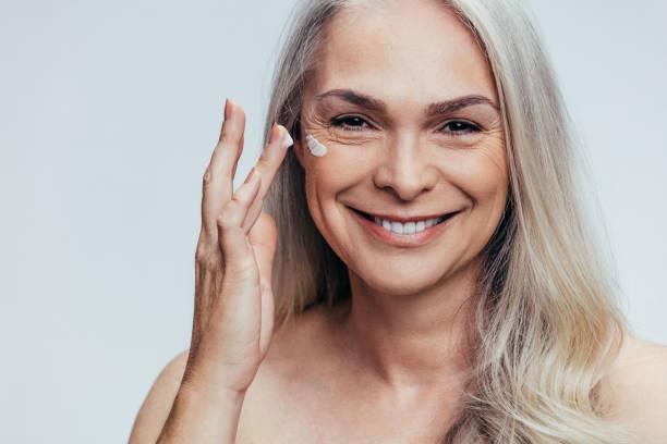 senior woman applying anti aging cream - mettersi lo smalto foto e immagini stock