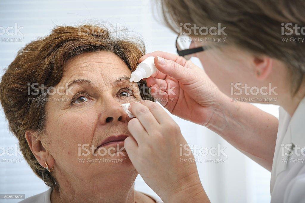 Senior woman applying eye drops stock photo