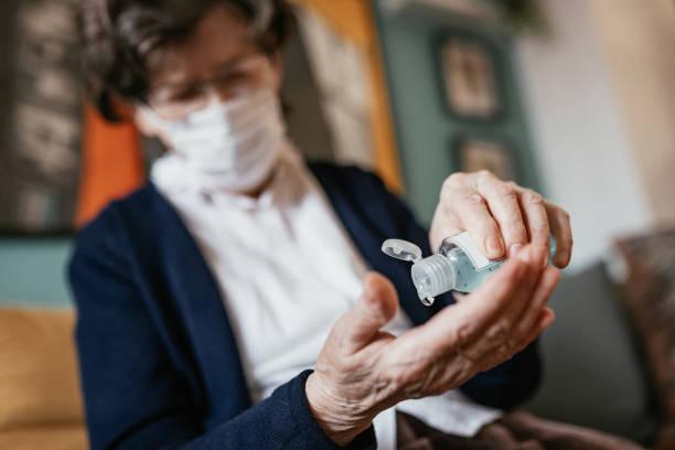 mujer mayor que aplica desinfectante de manos en casa - hand sanitizer fotografías e imágenes de stock