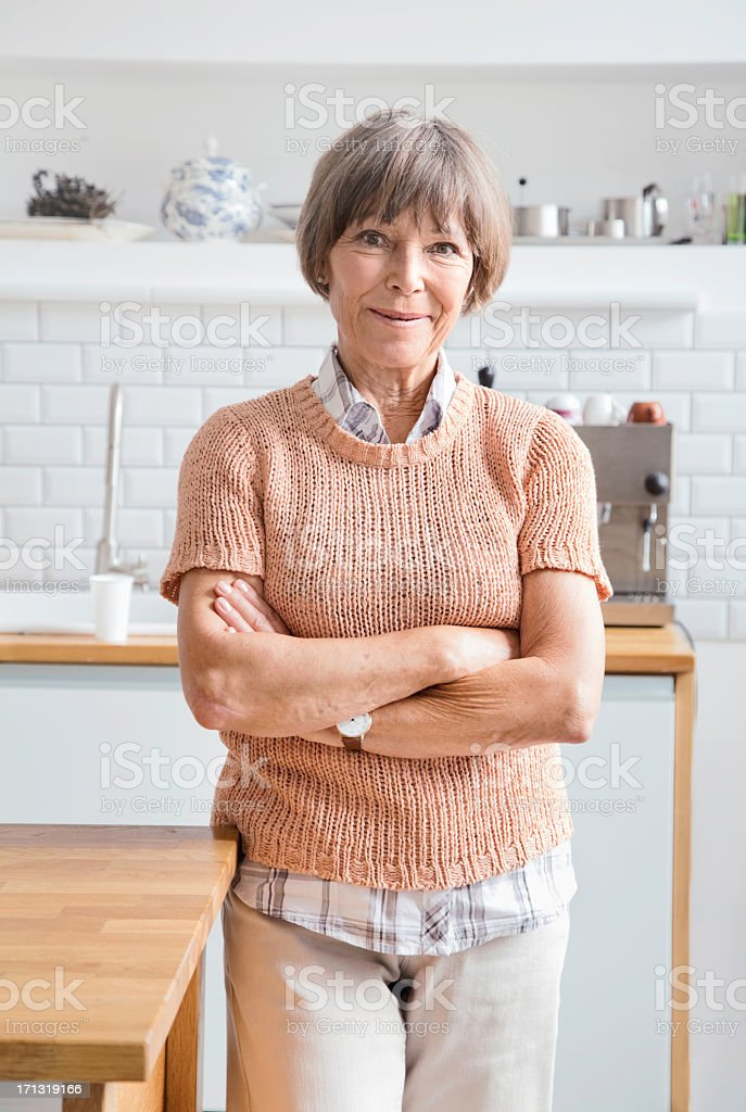 Senior woman arms crossed in kitchen smiling royalty-free stock photo