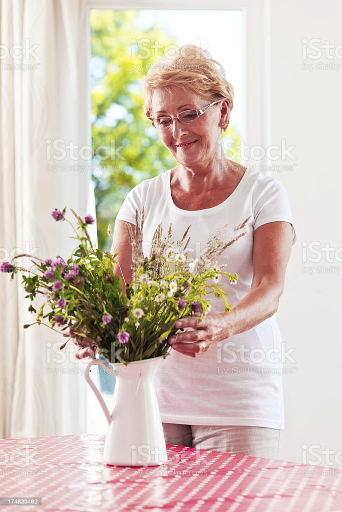 Senior woman arranging flowers royalty-free stock photo