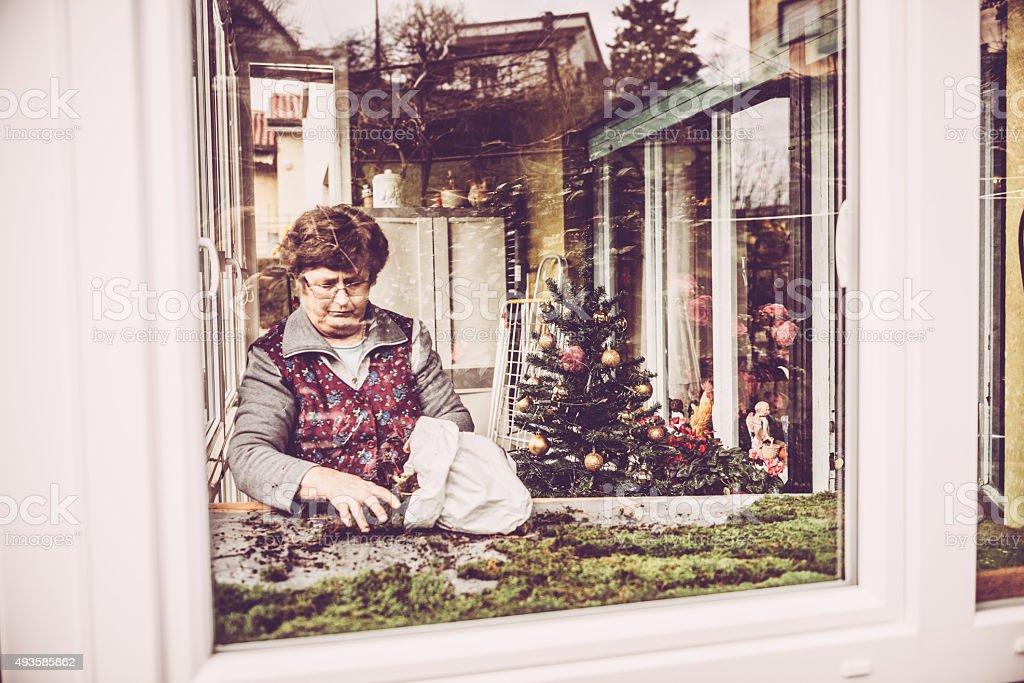 Senior  Woman Arranging Nativity Scene, Balcony, View through Window, Europe stock photo