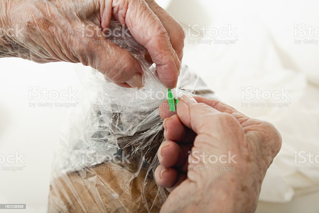 senior woman arthritis hands fastening twist-tie royalty-free stock photo