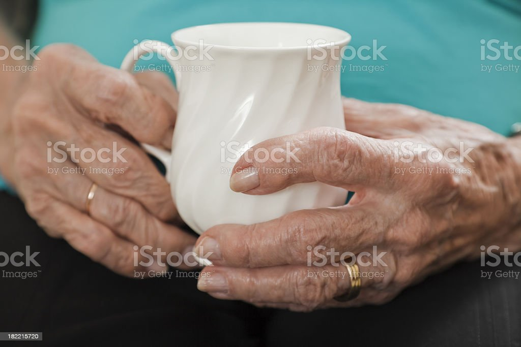 senior woman arthritis hands holding white coffee cup royalty-free stock photo