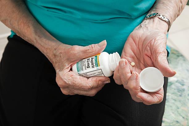 senior woman arthritis hands opening aspirin bottle stock photo