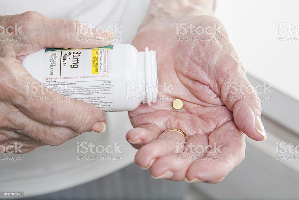 senior woman arthritis hands with one aspirin in hand close-up stock photo