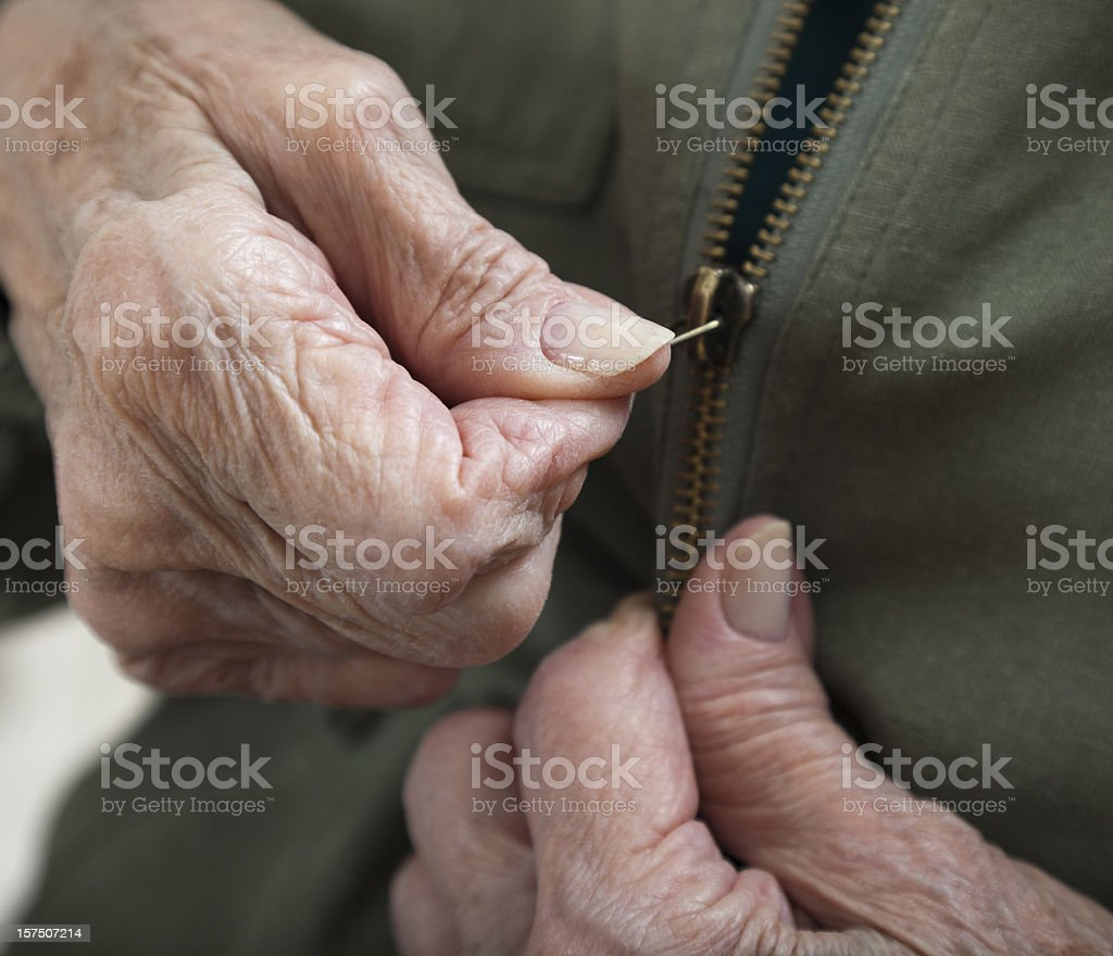 senior woman arthritis hands zipping zipper on jacket stock photo