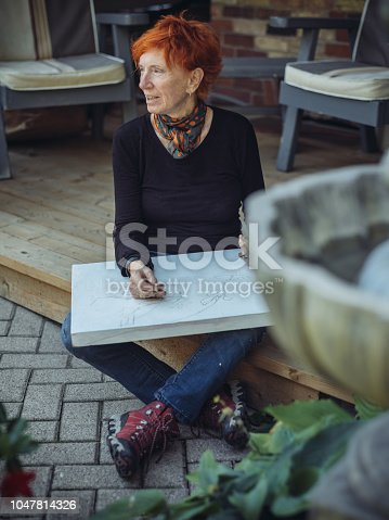Senior Caucasian woman artist with red hair, sketching  in front of her house.