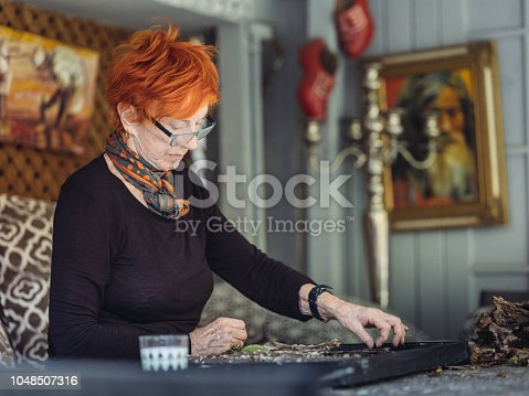 Senior Caucasian woman artist with red hair, creating painting in her studio.