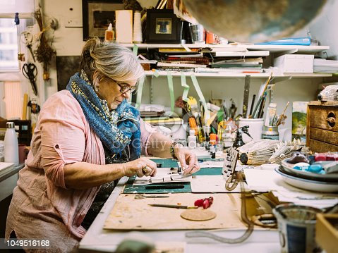Senior Caucasian woman artist , creating art installation in her studio. All art work featured in the image (collages, paintings, photos, sculptures) created by the woman in the photo.