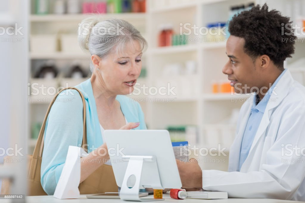 Senior woman asks pharmacy technician about cold medication stock photo