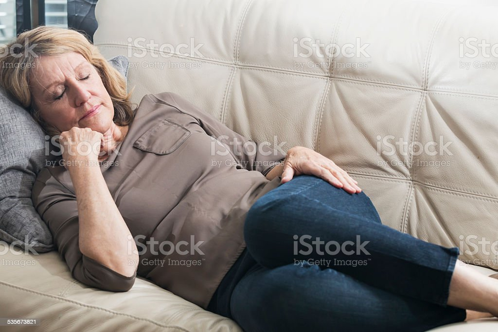 Senior woman asleep on the couch stock photo
