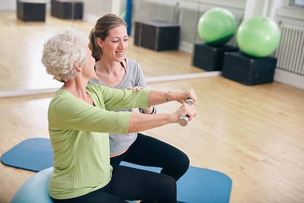 Senior Frau mit Betreuung durch personal trainer im Fitnessraum – Foto