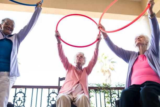 ältere frau bei einem fitness halten kunststoff reifen - hula hoop workout stock-fotos und bilder