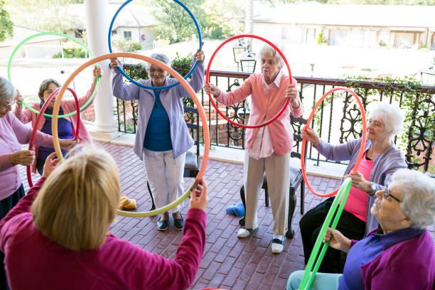 ältere frau in einem gruppe-fitness-klasse im freien - hula hoop workout stock-fotos und bilder