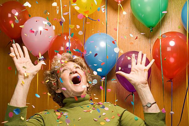 senior frau auf einer party - originelle geburtstagsgeschenke stock-fotos und bilder