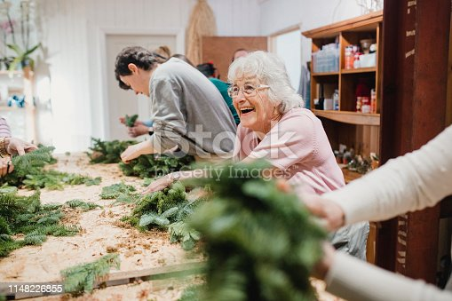 Senior woman is enjoying herself at a wreath-making workshop.