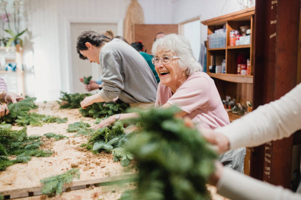 Senior Woman at a Wreath-Making Workshop Senior woman is enjoying herself at a wreath-making workshop. tradition stock pictures, royalty-free photos & images