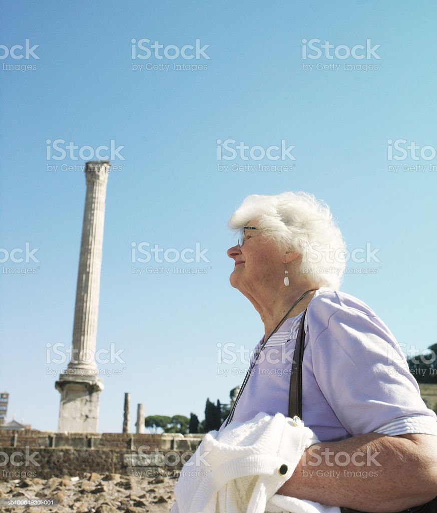 Senior woman at ancient site, side view foto de stock libre de derechos