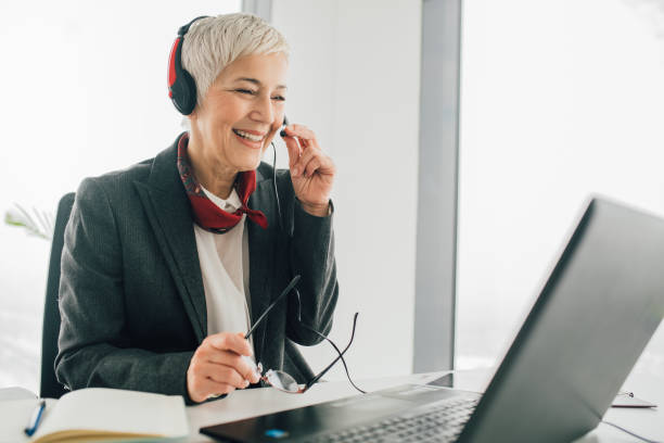 Senior woman at call center Smiling old business woman working at call center hands free device stock pictures, royalty-free photos & images