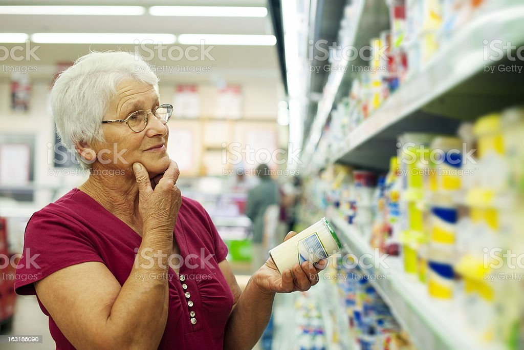 Senior woman at groceries store stock photo