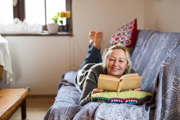 Senior woman at home lying on couch reading a book, relaxing Beautiful senior woman at home lying on couch reading a book, relaxing sole of foot stock pictures, royalty-free photos & images