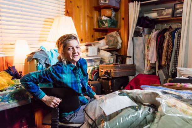 Senior woman at home, messy room A senior woman in her 60s at home, sitting in a messy, cluttered room, looking at the camera with a serious expression. greed stock pictures, royalty-free photos & images