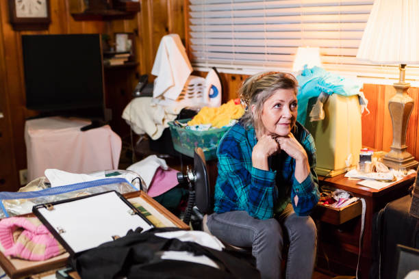 Senior woman at home, messy room A senior woman in her 60s at home, sitting in a messy, cluttered room, looking away with a serious expression. greed stock pictures, royalty-free photos & images