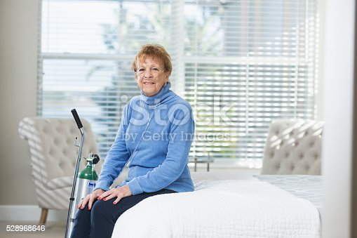 A senior woman in her 70s sitting in her bedroom with a portable oxygen tank. She is relaxed, smiling and looking at the camera.