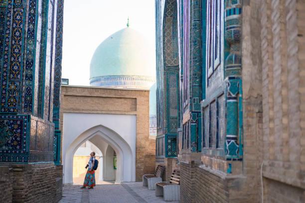 senior vrouw op memorial gebouwen van de shah-i-zinda mausolea in samarkand, oezbekistan - oezbekistan stockfoto's en -beelden