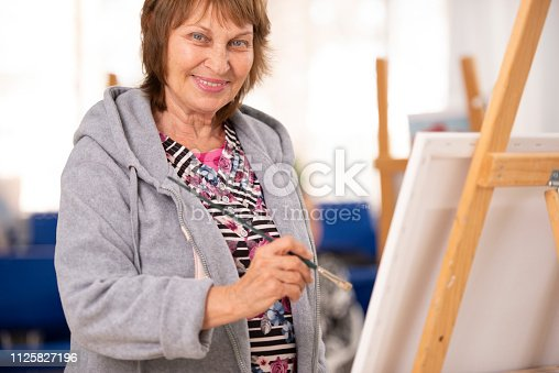 istock Senior woman at painting class. 1125827196