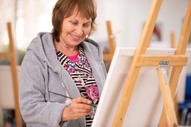 Senior woman at painting class. Happy senior woman painting on easel during an art lesson. alternative therapy stock pictures, royalty-free photos & images