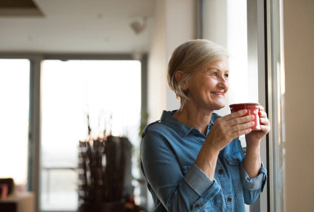 senior woman at the window holding a cup of coffee - tasse flat photos et images de collection